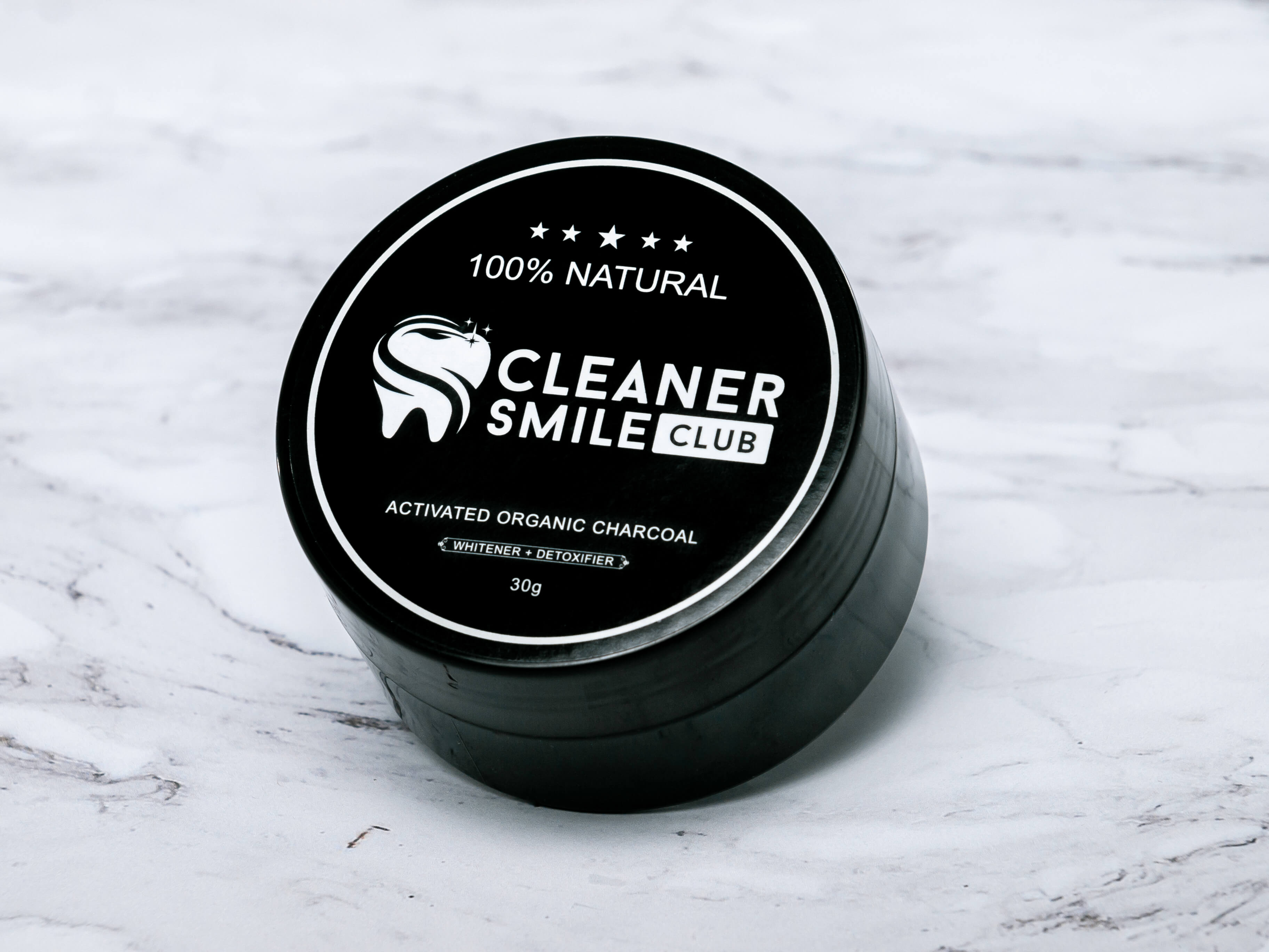 Best way to whiten teeth use charcoal powder black bottle from black kit of Cosmetic Brand Cleaner Smile Club, this bottle located on the marble background professional commercial photo made by Fantastic Imago Branding, Advertising and Consulting Agency