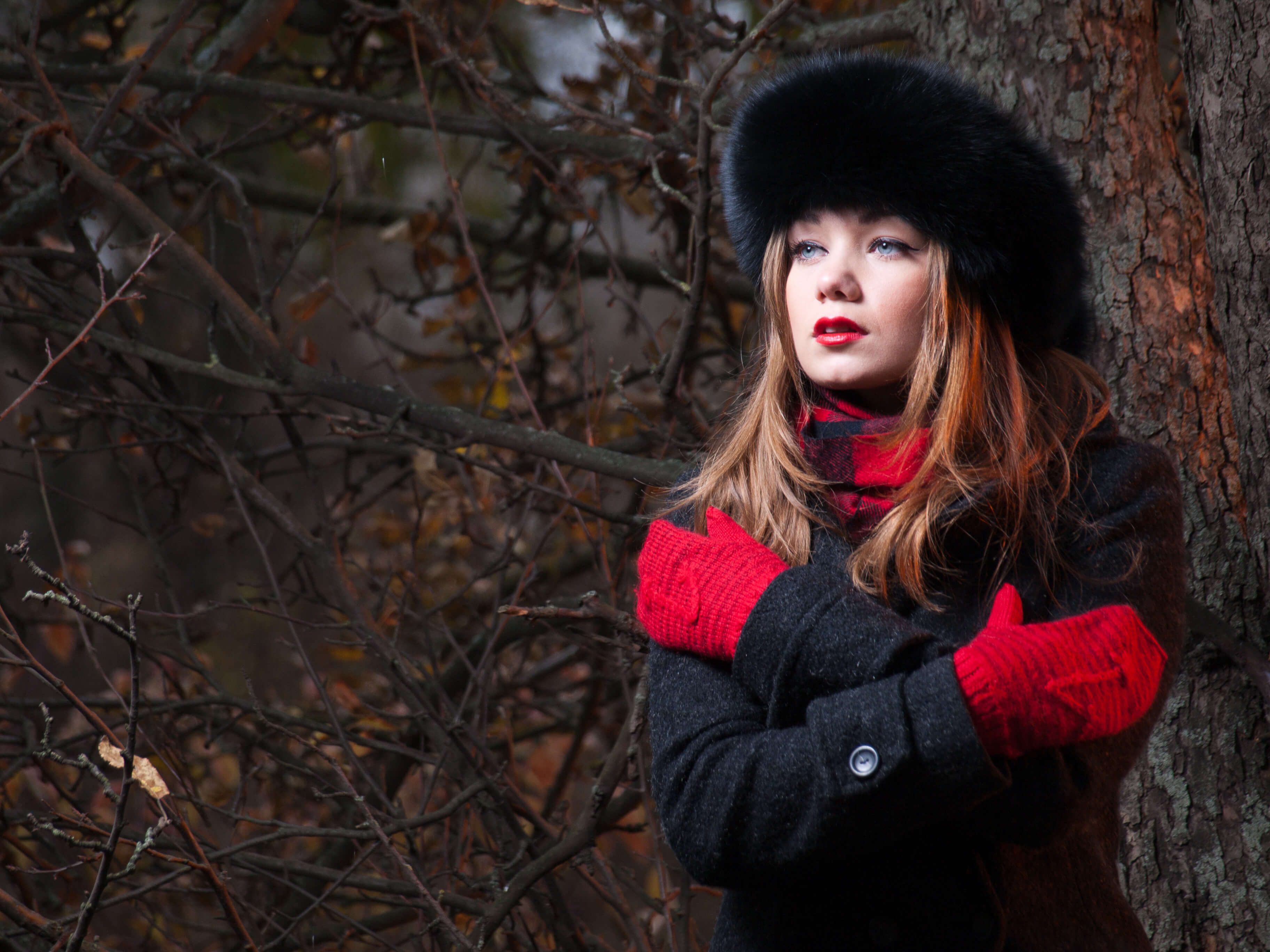 Commercial product photography model girl outdoors on the background of the forest dressed warmly in red gloves fur hat coat and scarf fashion pro photography made photo by Fantastic Imago Branding, Advertising and Consulting Agency